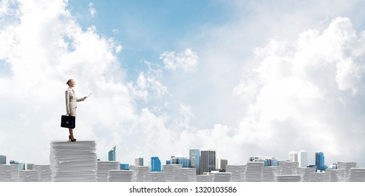 Confident business woman in suit standing on pile of documents with skyscape and city view on background. Mixed media.