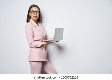 Confident business woman wearing pink suit standing by white wall holding opened laptop looking at camera