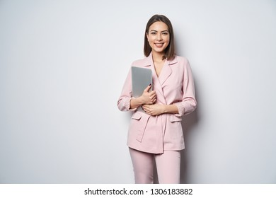 Confident business woman wearing pink suit standing by white wall with laptop underarm looking at camera