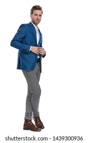Confident businessman adjusting his jacket's button while wearing a suit and standing with his legs crossed on white studio background