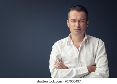 Confident businessman with arms crossed. Portrait of successful executive manager by the wall. Copy space.