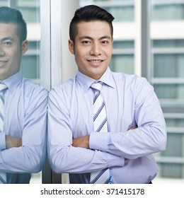 Confident businessman with arms crossed smiling