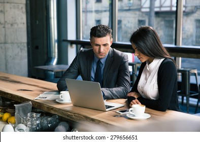 Confident businessman and attractive businesswoman working on laptop together in cafe