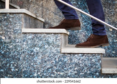 Confident businessman with bag walking the stairs. Man walking upstairs. Way to success. Man's legs. Man with bag climbing stairs. Success concept. Way up concept.