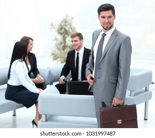 confident businessman with briefcase standing in the lobby of the office.