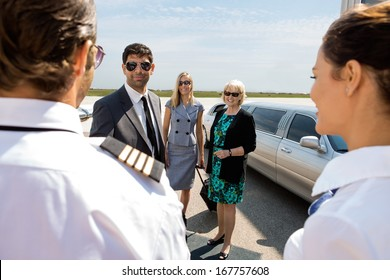 Confident businessman with colleagues greeting pilot and airhostess at airport terminal