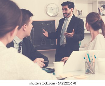 Confident businessman discussing new business project with members of his team