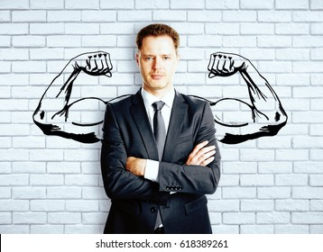 Confident businessman with drawn muscly hands on brick background. Strength concept