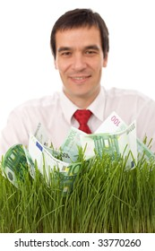 Confident businessman with euro banknotes in grass - focus on money, green business concept