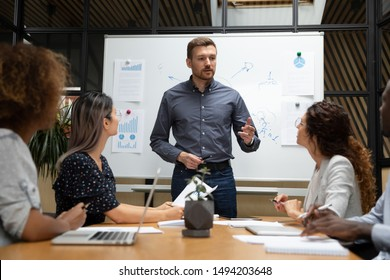 Confident businessman executive mentor ceo leader talk to employees group during corporate briefing in boardroom, serious male boss explain work plan to multiethnic workers at office meeting table