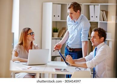 Confident businessman explaining his viewpoint to secretary