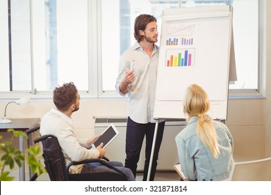 Confident businessman explaining multi colored graph on whiteboard while colleagues looking at it in meeting room in creative office
