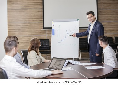 Confident businessman explaining something to colleagues at meeting
