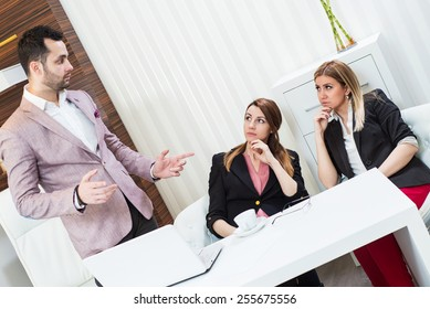 Confident businessman and his partners discussing something, he holds a master sentence.