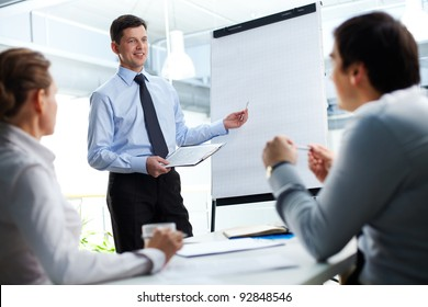 Confident businessman and his partners discussing something on a whiteboard