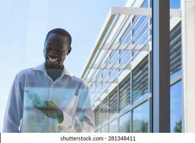 Confident Businessman holding cellphone through window of modern office