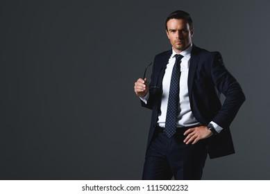 confident businessman holding eyeglasses isolated on grey background