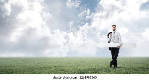 Confident businessman holding jacket behind his back in one hand and white big arrow in another hand while standing at green meadow and skyscape view on background.