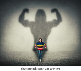 Confident businessman imagine himself a powerful hero, casting shadow of big strong muscular bodybuilder showing his biceps. Inner strength, leadership qualities. Business development.