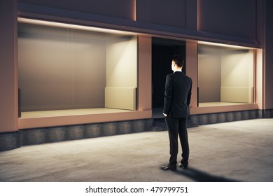 Confident businessman looking at empty clean storefront at night. Side view, Mock up, 3D Rendering