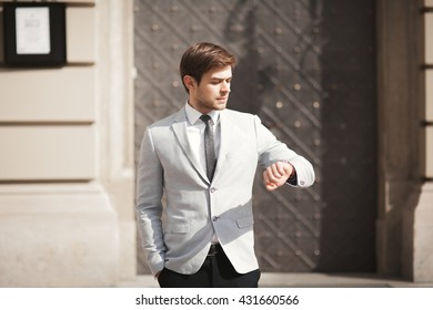 Confident businessman looking on his wrist watch in suit