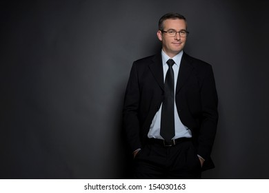 Confident businessman. Confident middle-age man in formalwear looking at camera while standing isolated on grey