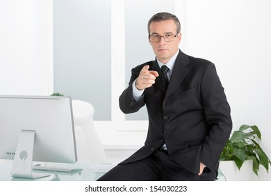Confident businessman. Confident middle-age man in formalwear pointing you while sitting at his working place