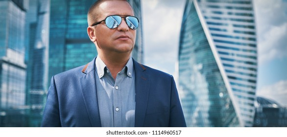 Confident businessman in a modern city with skyscrapers as background. Man wearing sunglasses. Urban lifestyle