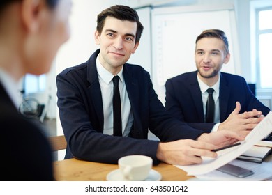 Confident businessman pointing at paper in his hand while listening to colleague