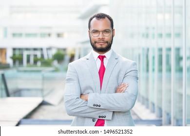 Vertrauter Geschäftsmann, der sich draußen mit gefalteten Armen posiert. Schöner junger lateinischer Geschäftsmann mit Brille und roter Krawatte und Kamera. Erfolgreiches Konzept für Geschäftsleute