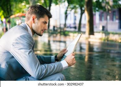 Confident businessman reading newspaper outdoors