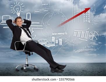 Confident businessman reclining in swivel chair in front of marketing flowchart in desert landscape