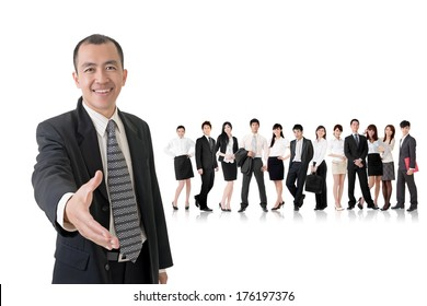 Confident businessman shake hand with you and standing in front of his team on studio white background.