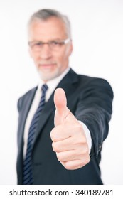 Confident businessman showing thumb up