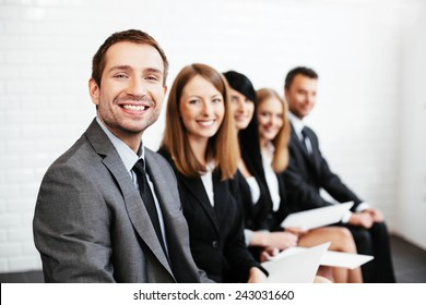 Confident businessman sitting with business partners in background