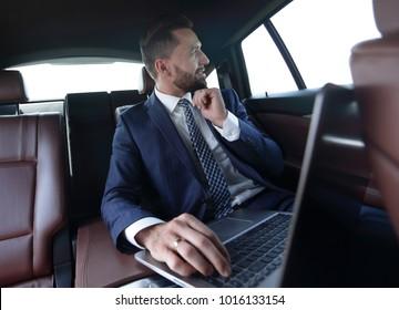 Confident businessman sitting in car
