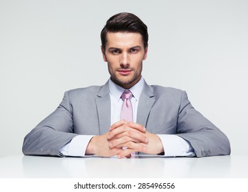 Confident businessman sitting at the table over gray background and looking at camera