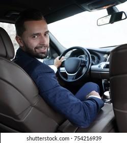Confident businessman sitting at the wheel of a prestigious car