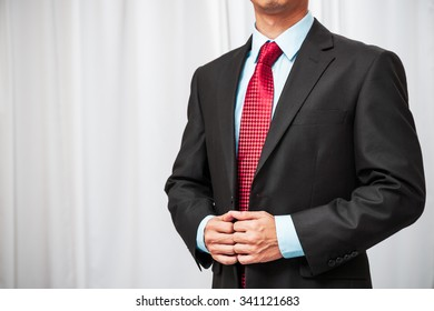 confident businessman standing formally holding his tuxedo