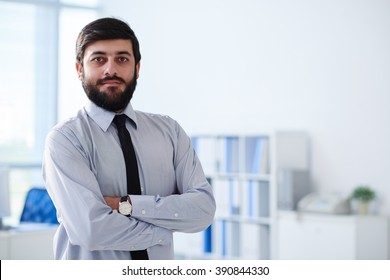 Confident businessman standing with his arms crossed