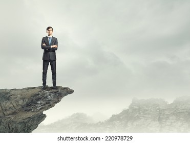 Confident businessman standing on top of rock