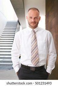 Confident businessman standing in shirt and tie, hands in pocket, looking at camera with a small smile.
