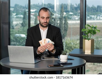 Confident businessman in suit holding a bunch of money cash ILS shekels. Time investment, wage, loan and bribery concept. Achievement career wealth. Copy space for advertisement.
