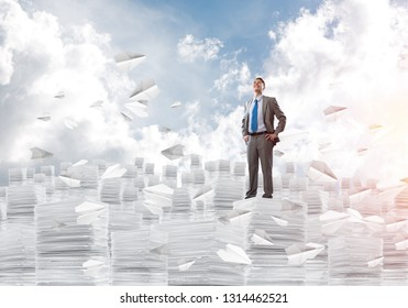 Confident businessman in suit standing among flying paper planes and looking away with cloudly skyscape on background. Mixed media.