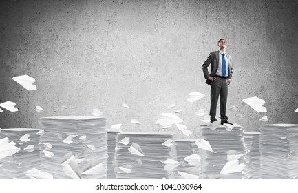 Confident businessman in suit standing on pile of documents among flying paper planes with grey background. Mixed media.