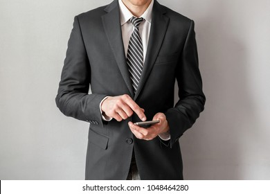 Confident businessman in suit using smartphone over grey background.