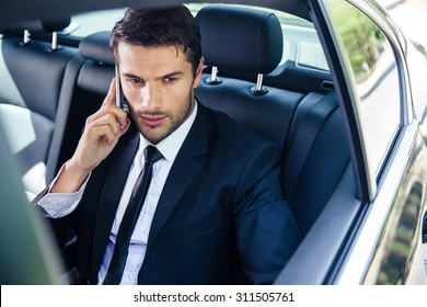 Confident businessman talking on the phone in car