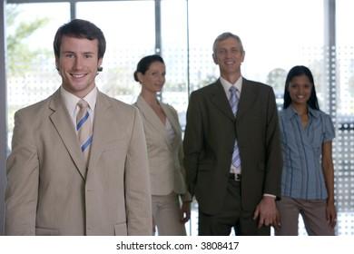 Confident businessman with team behind him