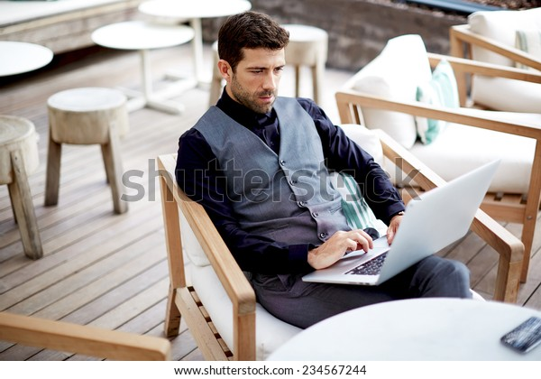 Confident businessman typing on laptop computer keyboard working, caucasian business man in suit sitting at work break in cafe with computer, businesspeople using technology, success concept