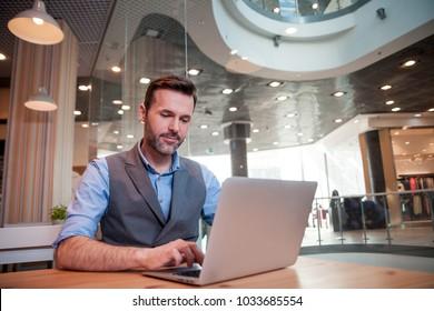 Confident businessman using laptop computer in modern interior